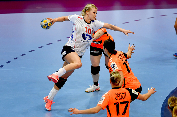 A Norwegian handball player gearing up to throw the ball at a game in the European Women's Handball Championship.