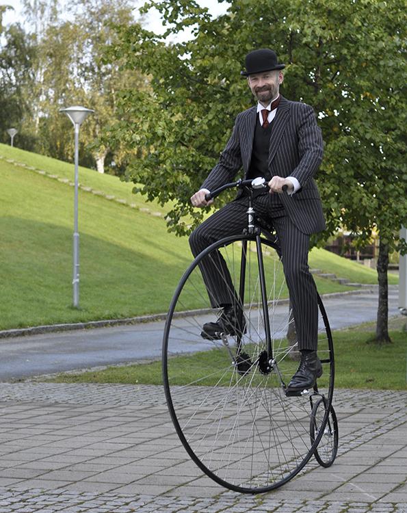 Man on a high-wheeler velocipede.