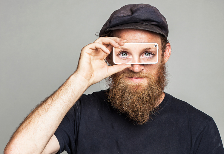 A man covering his eyes with a phone showing a different set of eyes.