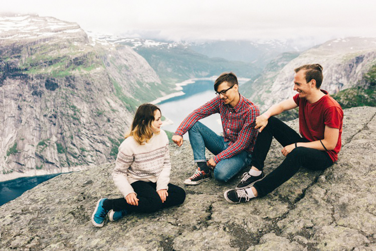 Three people sitting above the fjords.