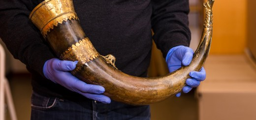A man holding an ancient buffalo horn.