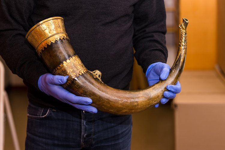 A man holding an ancient buffalo horn, which may be one of the Viking artifacts at Disney World.
