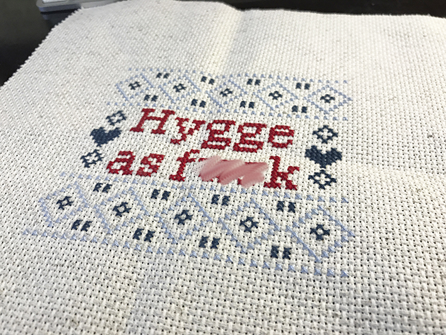 "Cross-stitch in a Nordic pattern that reads ""hygge as fuck"" (though part of the word ""fuck"" has been blurred"