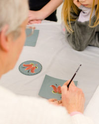 A woman teaching a young girl rosemaling.
