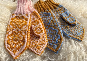 two pairs of selbu knitted mittens, one pink and one blue