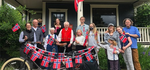 A group of people holding Norwegian flags standing on a front porch
