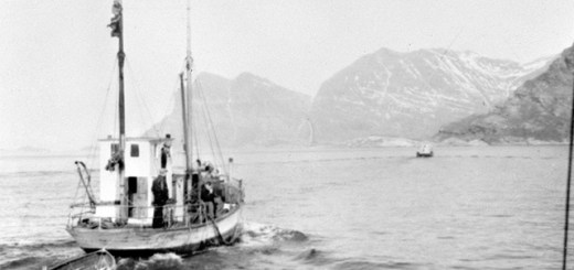 a fishing boat sailing in a fjord with mountains in the background