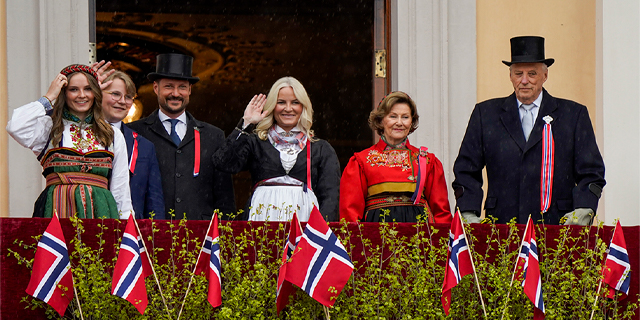 the Norwegian royal family waves from the balcony of the Royal Palace in Oslo