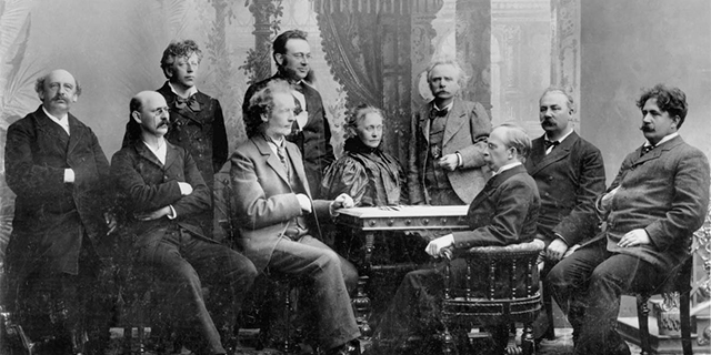 a black and white photo of Agathe Backer Grøndahl and Edvard Grieg at a table with other composers and musicians