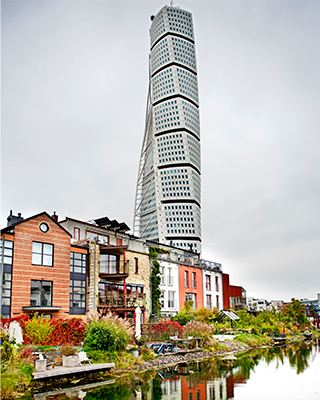 The Turning Torso tower behind a row of rowhouses in Malmö in Skåne county