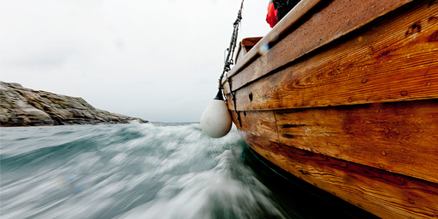 an image of the side of a boat as it speeds along the water