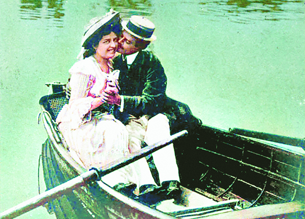 A man and a woman kissing in a boat in an old photograph
