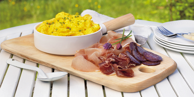 a koldtbord of scrambled eggs and varies sliced meats