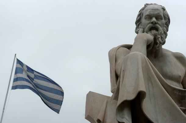 "A Greek flag flies next to a statue of ancient Greek philosopher Socrates in the center of Athens on 23 May, 2012. International Monetary Fund (IMF) chief Christine Lagarde warned on May 23 of the risk of ""contamination"" if Greece quits the euro and said the eurozone might therefore see the value of paying more to keep Greece in. AFP PHOTO / ARIS MESSINIS (Photo credit should read ARIS MESSINIS/AFP/GettyImages)"