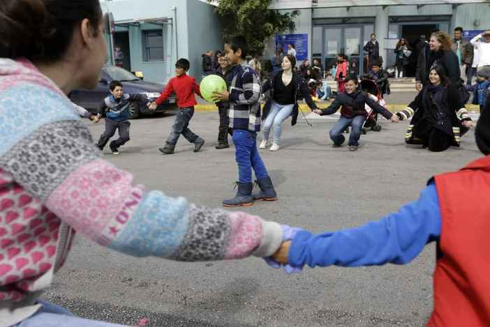 Greek pupils and their teacher play with refugee children in Piraeus, near Athens, Tuesday, March 8, 2016. European Union leaders hoped early Tuesday they reached the outlines for a possible deal with Ankara to return thousands of migrants to Turkey and said they were confident a full agreement could be reached at a summit next week. (AP Photo/Thanassis Stavrakis)