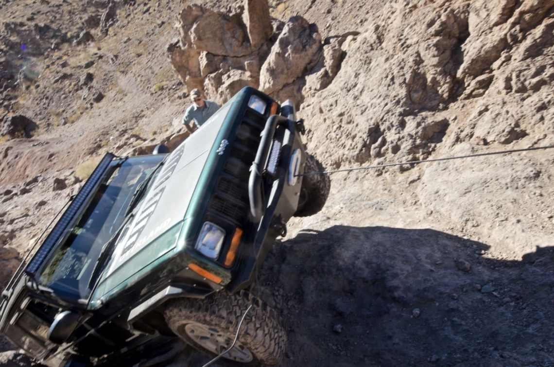 Jeep Cherokee getting winched up a ledge on Doran trail near Calico