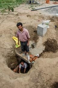 """Das """"Manhole"""" wird gemauert. Unten der Meister, oben der Handlanger."""