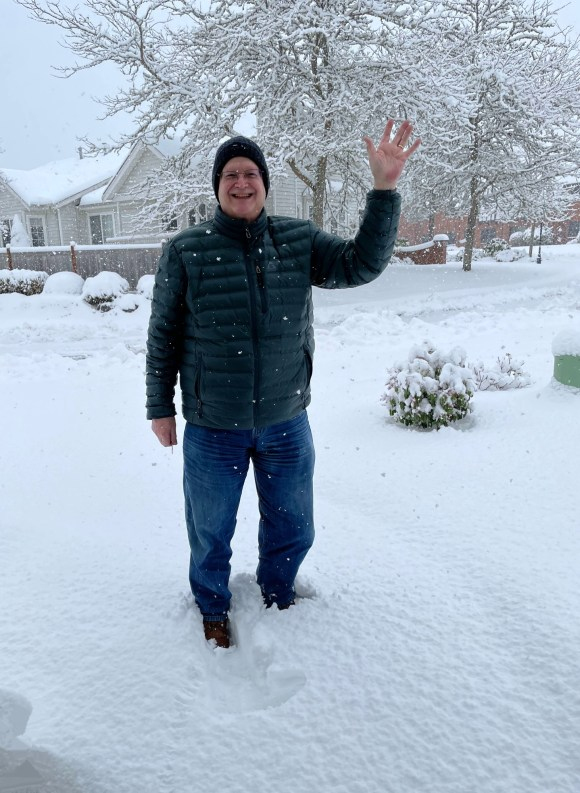 Man standing in snow waving while snow continues to fall