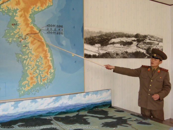 North Korean General points out the DMZ on a Map of the Korean Peninsula.