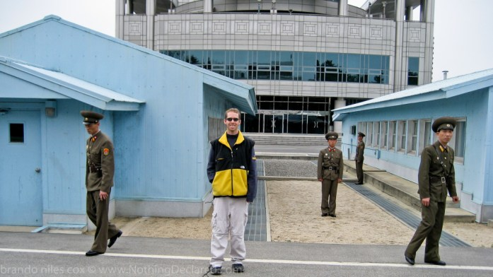 Author Brandon Cox stands in front of the blue UN buildings at the Military Demarkation line inside the DMZ's Joint Security Area