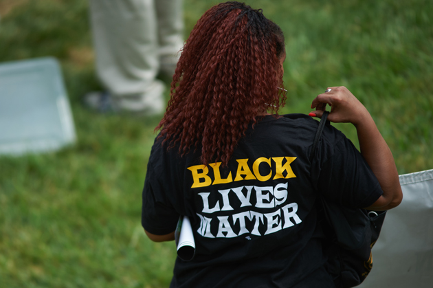 A woman wears a shirt with 'Black Lives Matter' during a memorial service for slain 18 year-old Michael Brown Jr. on August 9, 2015 at the Canfield Apartments in Ferguson, Missouri.  Several hundred demonstrators stood in silence Sunday at the spot where an unarmed black teen was shot and killed by a white police officer one year ago, throwing America's troubled race relations into harsh relief. Two white doves were released over the crowd that gathered to mark the anniversary of 18-year-old Michael Brown's death in a fateful encounter August 9, 2014 with white police officer Darren Wilson. The crowd, about 300 strong, observed four and a half minutes of silence, one minute for each of the four and a half hours that Brown's body lay face down in the street before being taken away. AFP PHOTO / MICHAEL B. THOMAS