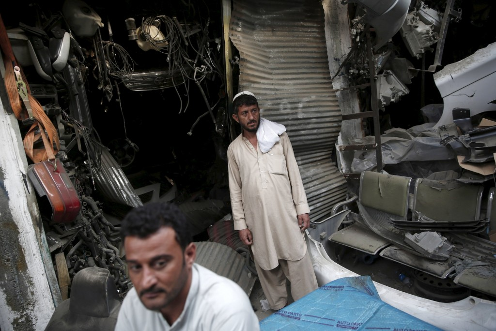 Afghan men stand next to damaged shops near the site of a truck bomb blast in Kabul, Afghanistan