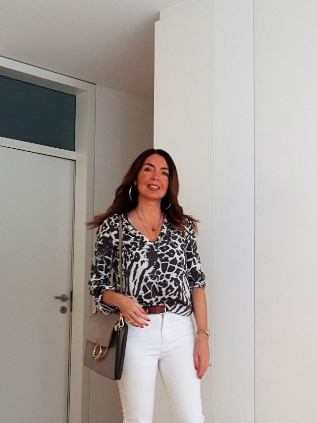 Oufit primaverile con jeans bianchi, blusa fantasia e borsa Chloé Faye