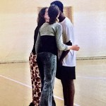 African american man being kissed by two white Lithuanian women after basketball game