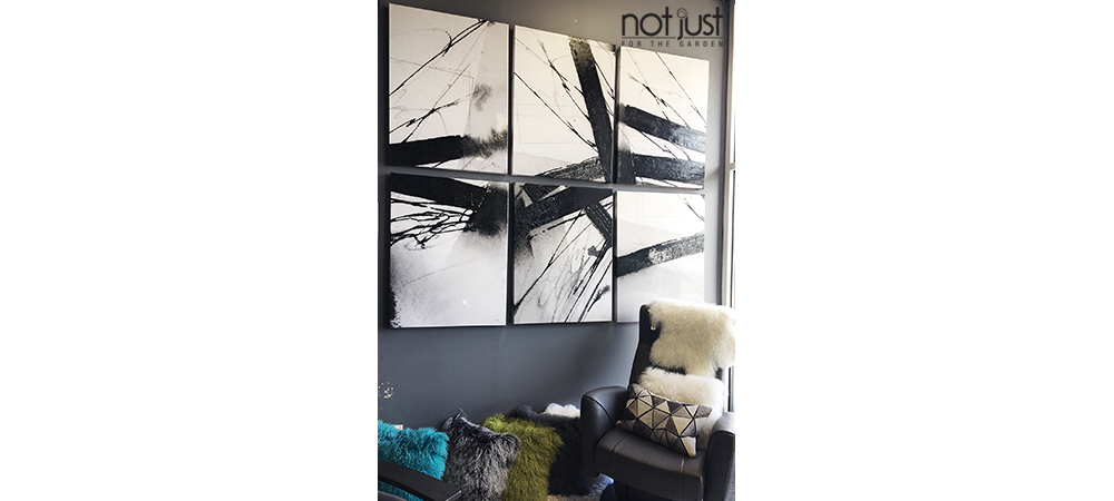 Three-piece narrow abstract paintings side by side of black stripes of various widths in different directions on a white canvas, mounted in vertical direction in a living room next to an accent chair