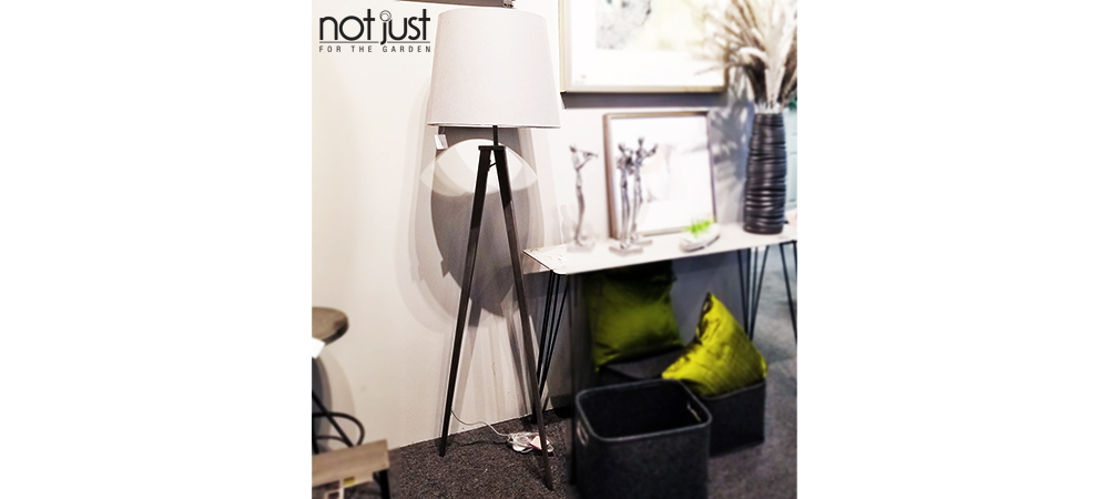 Origina Tripod Floor Lamp with white shade and black base next to framed art and console in a home decor setting