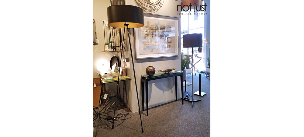 Origina Canada tripod floor lamp with black linen shade next to framed art and console in home decor setting