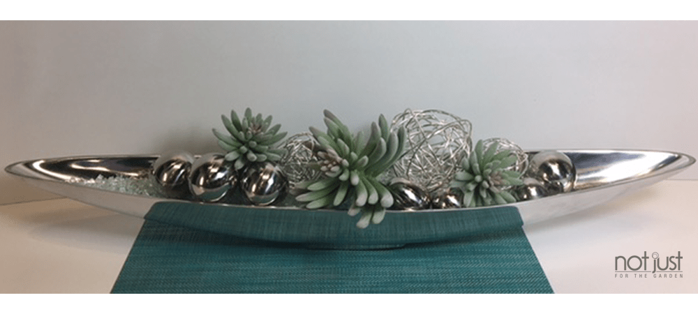 Contemporary table centerpiece with faux succulents, metal spheres and wire balls over a green placemat