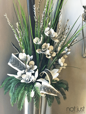 Interior arrangement with bright green branches and faux foliage in tall silver planter