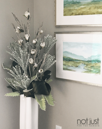 Interior arrangement with tall white vase and winter coloured voliage next to scenic framed paintings in an interior decor setting