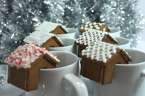 gingerbread house that sits on the rim of a mug