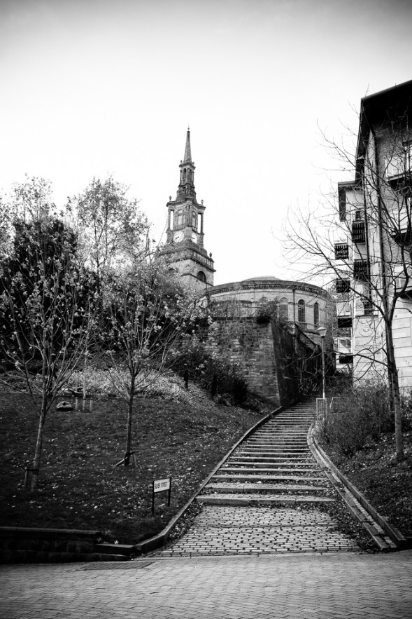 A cobbled street separates old churches from new office blocks.