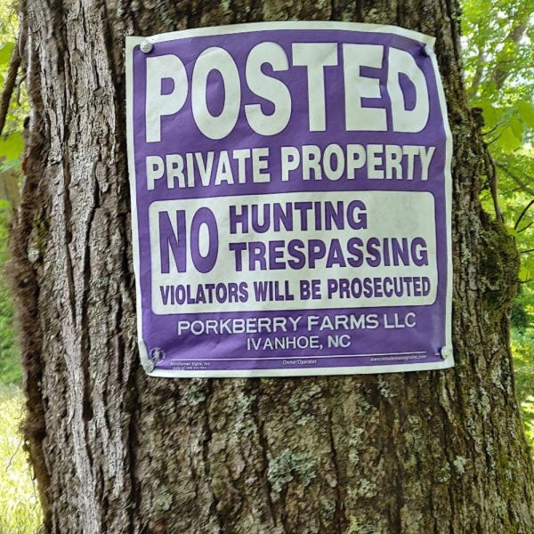 Posted Private Property No Hunting Trespassing Violators will be Prosecuted Purple Tyvek Sign wrapped around a tree