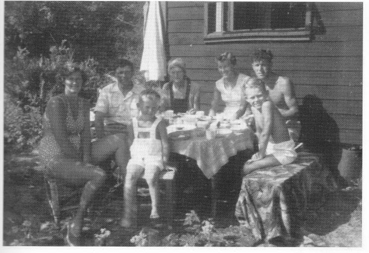I 1945 satte byggmester Nils Kamfjord fra Nesbrygga opp denne lille hytta på 5 kvadratmeter i Halvsreinshavn. Den var ment som utgangspunkt for fiske- og jaktturer, men ble snart tatt i bruk på den flyktningtransportruta som gikk over Nesbrygga til Havstensund. På feriebildet fra 1954 ser vi Reidar og Elfrida Rostad, datteren Reidun til venstre, barnebarna Reidar og Thor-Ove, Solveig Kjærnes og sønnen Kjell til høyre.