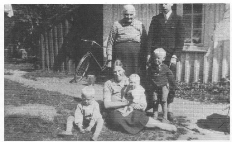 Gårdsplassen i Kjølelia 1929. Bak: Bestemor Anne Helvig Johannessen og fet-ter Harald Olsen (Ryller) fra Oslo. Foran fy. Reidar, Ragnhild med Tore på fanget og Helge. (Foto utlånt av Tore Paulsen.)