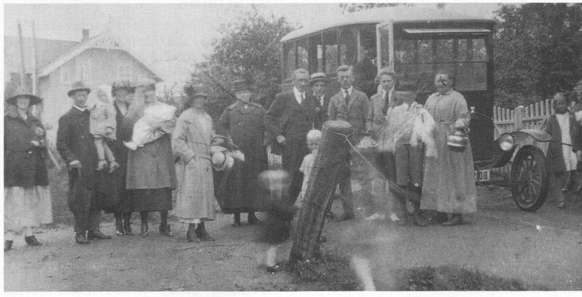 Rutebilen i Årøsund 1926 eller 27. Familien Olsen fra Vestfoldgaten i Tønsberg er på besøk hos sin familie i Årøsund. Sjåføren, som står i bildøren, er Marinius Hansen «Snilde Hansen» far til rutebileier John Elmer. (Foto utlånt av Ragnar Wrige.)