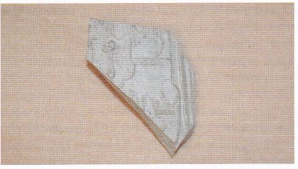 Keramikk av Siegburg-type som kan dateres til slutten av 1500-tallet. Skåret stammer fra et høyt, smalt drikkekrus som var rikt dekorert: Til venstre ses et våpenskjold og til høyre en krone. Over denne skimtes i overkant av skåret beina til en løve. Denne type kar var nok ikke eid av hvem som helst. (Foto: Eli Ulriksen.)