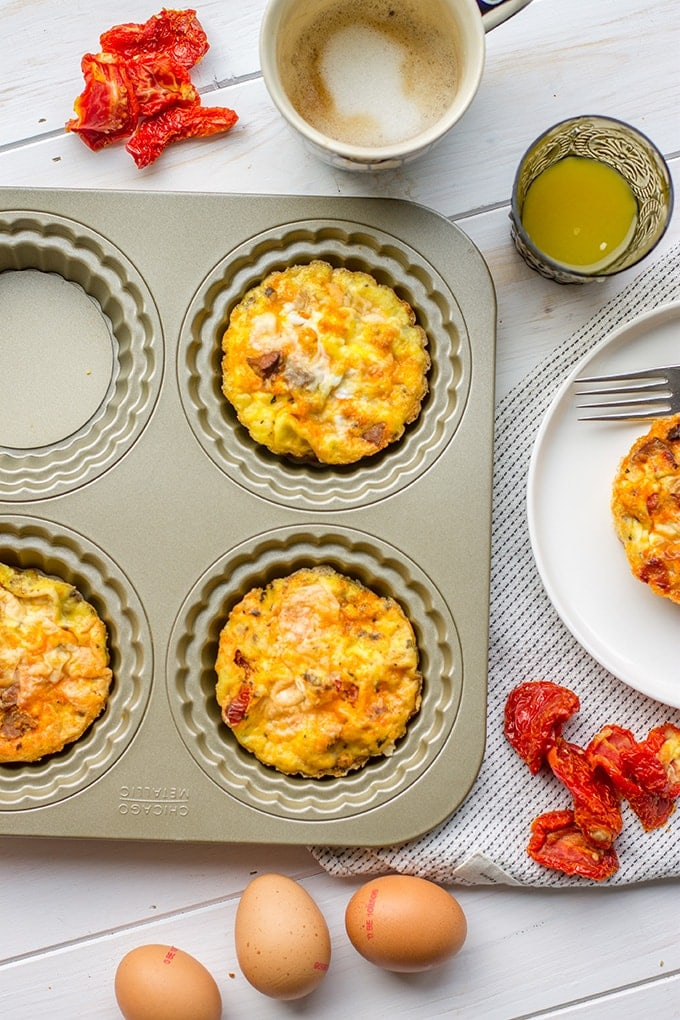 A pan of chorizo sun-dried tomato mini frittatas, surrounded by coffee, orange juice, and eggs.