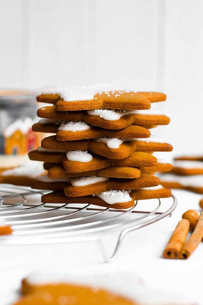 Gingerbread star cookies stacked in a tower on top of a silver, round cooling rack.