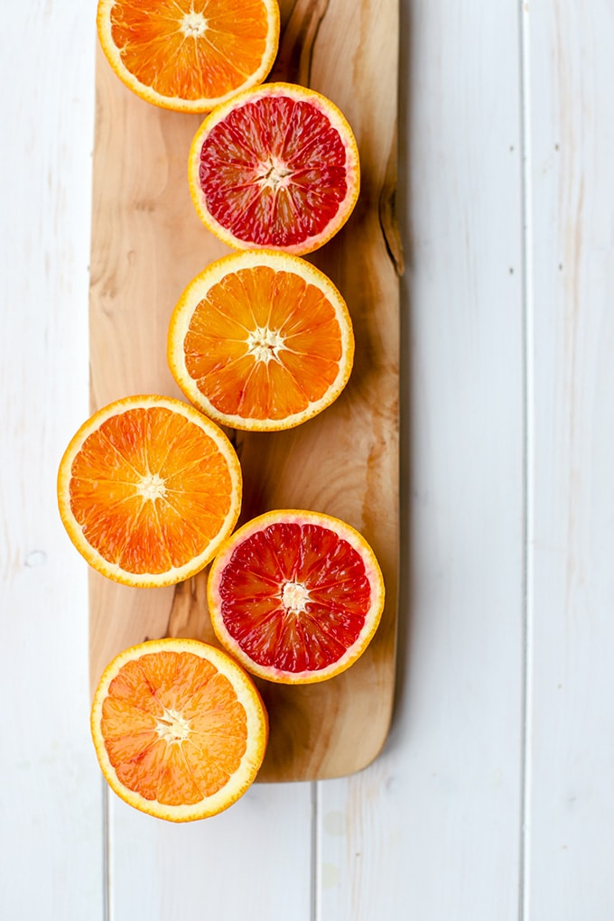 Brilliant pink and red blood oranges, sliced open and arrayed on a narrow cutting board.