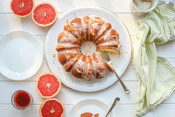 Flat-lay photo of glazed grapefruit bundt cake, cut and served with coffee, fresh grapefruit, and juice.