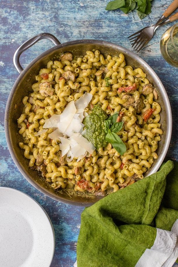 Hero image for the best classic pesto cavatappi recipe - a large skillet full of the dish, with serving plates, forks, and a bold green kitchen towel nearby.