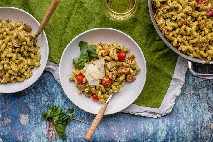 Flat-lay of white dinner plate filled with homemade pesto cavatappi.