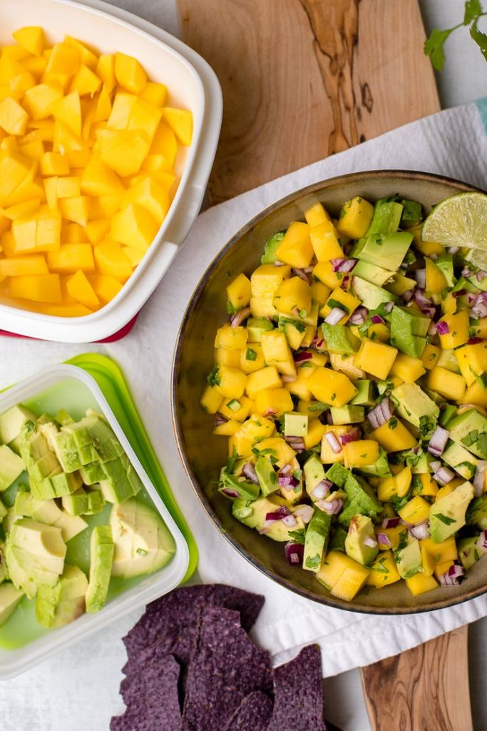 A large bowl full of fresh mango avocado salsa, with tupperware off to the side containing plain mango and plain avocado.