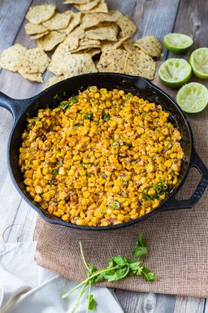 A cast-iron skillet filled with skinny chipotle corn dip, surrounded by tortilla chips and juiced limes.