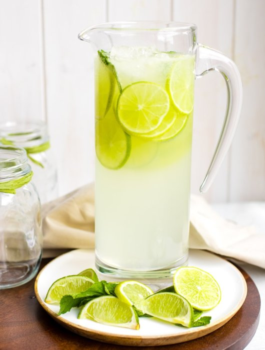 A tall glass pitcher filled with sparkling limeade.